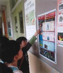小学校の廊下に掲示された壁新聞を読む子供達の様子